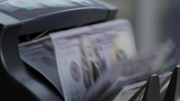 closeup tiro de máquina de contagem de dinheiro com notas de 100 dólares. video