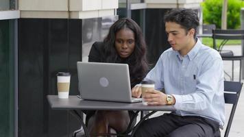 dos jóvenes empresarios sentados en una reunión en la cafetería al aire libre video