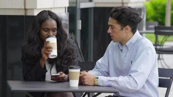 Two young business people sitting an meeting at outdoor cafe video