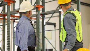 Dos contratistas industriales mirando los planos y el progreso de la construcción video