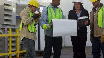 El equipo de construcción comercial revisa los planos. video