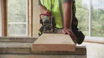 Closeup of construction worker cutting with circular saw video