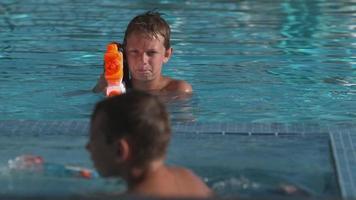 meninos lutando com revólver na piscina, super câmera lenta video