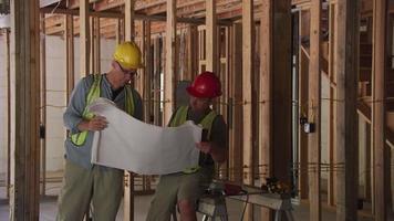 trabajadores de la construcción mirando planes juntos video