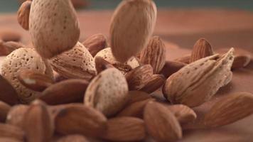 Almonds falling onto wooden surface in super slow motion.  Shot on Phantom Flex 4K high speed camera. video