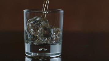 el whisky se vierte sobre hielo en cámara lenta filmada en phantom flex 4k a 1000 fps video