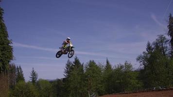Motocross racer going over big jump in slow motion 4K fully released video