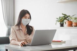 Mujer asiática con mascarilla trabajando en casa durante la cuarentena por coronavirus foto