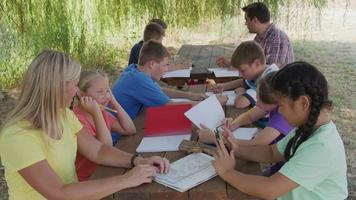 Kids at outdoor school writing in notebooks video