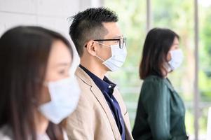 Fila de asiáticos con máscaras protectoras para la seguridad foto
