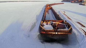 Aerial shooting of an old ship barge on a frozen river video