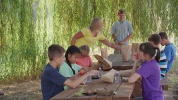 niños en la escuela al aire libre almorzando juntos video