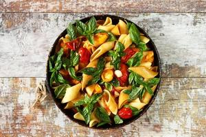 Pasta in a pan with tomatoes basil and spices photo