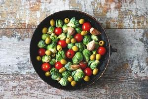 Brussel sprouts with vegetables and herbs in a pan photo