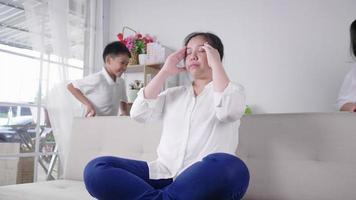 les enfants sont fatigués et courent près d'une mère contrariée assise sur un canapé frustrante maman stressante ressent de la lourdeur et des maux de tête à la maison fatigue le parent ne veut pas jouer avec son fils et sa fille video
