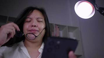 femme asiatique stressée assise et utilisant un smartphone travaillant dur pour essayer de résoudre le problème dans la salle de travail la nuit en recherchant sur Internet et en discutant video