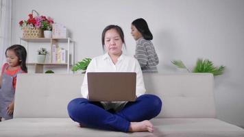 mère calme s'asseoir sur un canapé travaillant sur un ordinateur portable petits enfants jouent autour d'une maman paisible se détendre sur un canapé utiliser un ordinateur moderne distrait du bruit concept d'éducation parentale video