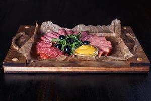 Salchicha cortada con hierbas y salsa en una bandeja de madera, hermosa porción, fondo oscuro foto