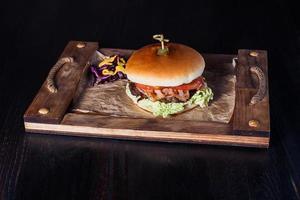 Hamburguesa con queso en una bandeja de madera en un restaurante, sobre un fondo oscuro foto