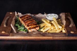 salmon fillet steak with french fries on a wooden tray, beautiful serving, dark background photo