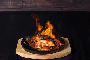 fajitos, meat in a frying pan with fire on a wooden tray, beautiful serving, dark background photo