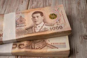 Pila de billetes de baht tailandés sobre fondo de madera foto