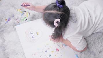 Vista superior del niño tirado en el suelo haciendo pintura con lápices de colores en la sala de estar con mucha actividad artística de felicidad en casa video
