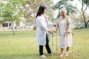 Médico ayuda y cuidado anciana asiática mayor o anciana mujer usa andador con una salud fuerte mientras camina en el parque foto