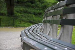 Curved green wooden bench in a park in the summer photo
