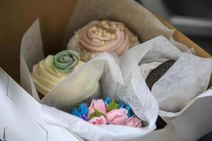 Variety of delicious cupcakes in a box from a pastry shop photo