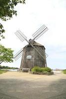 antiguo molino de viento de madera cerca del océano en el verano foto