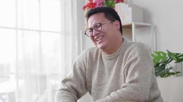homem rindo e sentado no sofá e passando um tempo assistindo série de comédia durante o dia em casa no fim de semana sozinho feliz humor video