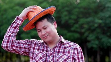adulto asiático em pé, sorriso, agricultor, feliz, olhando para a câmera, em, área cultivada, agrícola, macho, camisa xadrez vermelha, chapéu, sol, sol, ao ar livre, no verão video