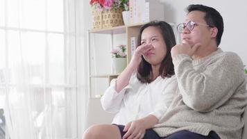 couple asiatique assis sur un canapé et pleurant en regardant un film dramatique triste à la télévision à la maison en quarantaine et concept de sécurité video
