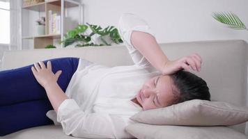 Mujer asiática insalubre acostada en el sofá en casa sufre de depresión o ansiedad infeliz lucha femenina milenaria con migraña o dolor de cabeza problema de salud concepto de dolor video