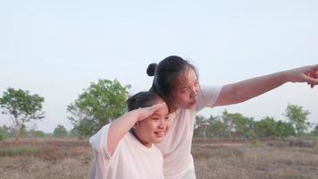 Front view of Asian mother point out and tell to daughter to looking far at field forest landscape then girl looking and point fingers follow mom Mum and kid close embrace with smile and happy video