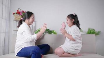 mom and kid sitting and playing hands game together with happy and laughing face on sofa in living room at home Mom and kid having fun activities concept video