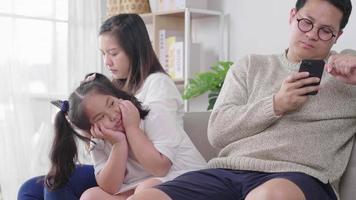 família sentada no sofá na sala de estar pai ignorando uma criança por estar no smartphone jogando e comprando online sem cuidar da cara de criança entediada video