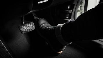 Foot pressing foot pedal of a car photo