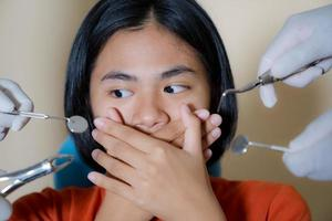 Girl frightened by dentists covers her mouth in dentist office photo