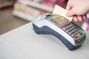 Deslizar la mano con tarjeta de crédito en el terminal de pago en la tienda foto
