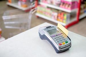 mediante deslizar la tarjeta de crédito en el terminal de pago en la tienda foto