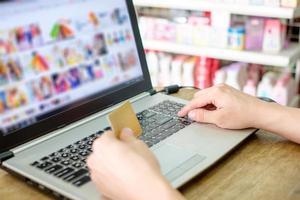 mano que sostiene la tarjeta de crédito y el uso de la computadora portátil pago compras en línea foto