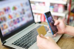 mano que sostiene la tarjeta de crédito y el uso de una computadora portátil con un teléfono inteligente para realizar compras en línea foto