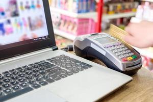 Deslizar la tarjeta de crédito con la mano en ternimal y usar el pago de una computadora portátil para comprar en línea foto