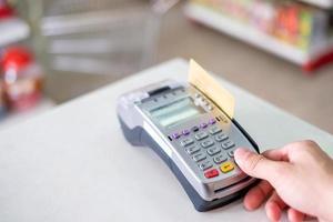Prensa manual deslizando la tarjeta de crédito en el terminal de pago en la tienda foto