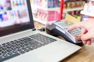 prensa manual deslizando la tarjeta de crédito en ternimal y usando la computadora portátil para realizar compras en línea foto