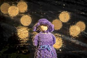 Wooden doll with crocheted blue dress against blurred background with bright lights photo