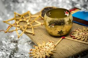 Golden Christmas decoration with straw stars candlesticks and matches with shiny silver background photo