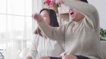 heureux petit ami et petite amie asiatiques regardant un match de football américain à la télévision à la maison couple riant ensemble match de football excité video